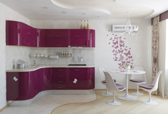 This lovely feminine kitchen in brilliant pink and white features a tiny dining area furnished with small modern furniture.