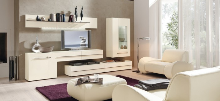 Sophisticated modern seating and media/display units in creamy white brighten this open living room while a purple area rug adds a burst of color to the monochromatic space.