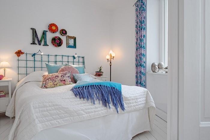 The bedroom is eclectically decorated with bright colors and differing styles for an overall relaxed appeal.