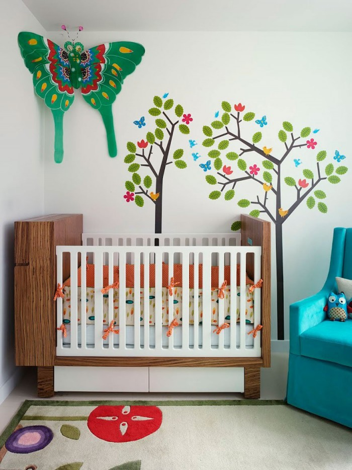 A colorful baby girl's nursery features a nature motif with trees on the walls, leaves on the bedding and a floral rug.