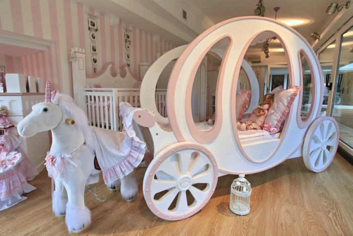 A fairy tale nursery features a crib and a carriage toddler bed to accommodate a growing child or two children of different ages.
