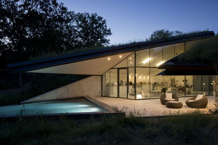 house built into hill moonlit pool