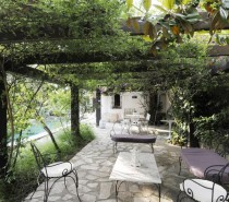 Pergola with cast iron outdoor furniture and twining climbers