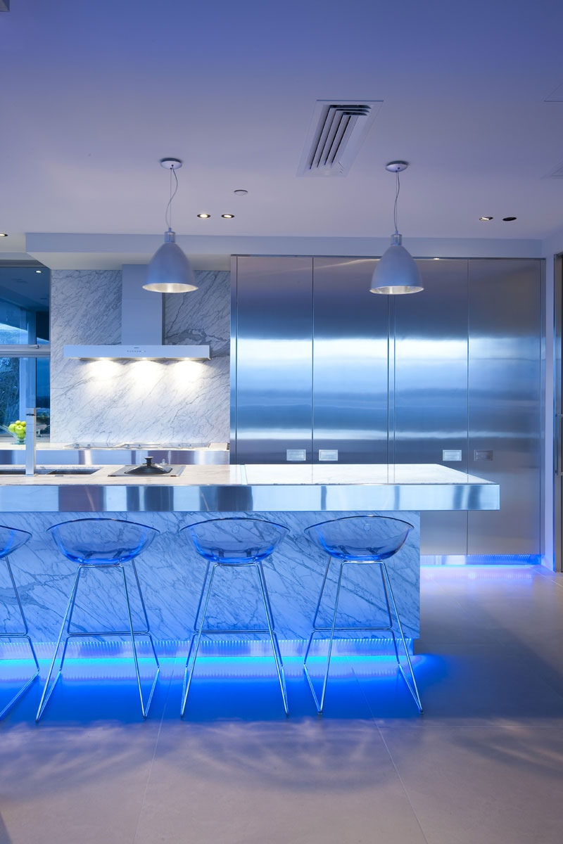the designer chose blue led lighting to infuse this modern kitchen