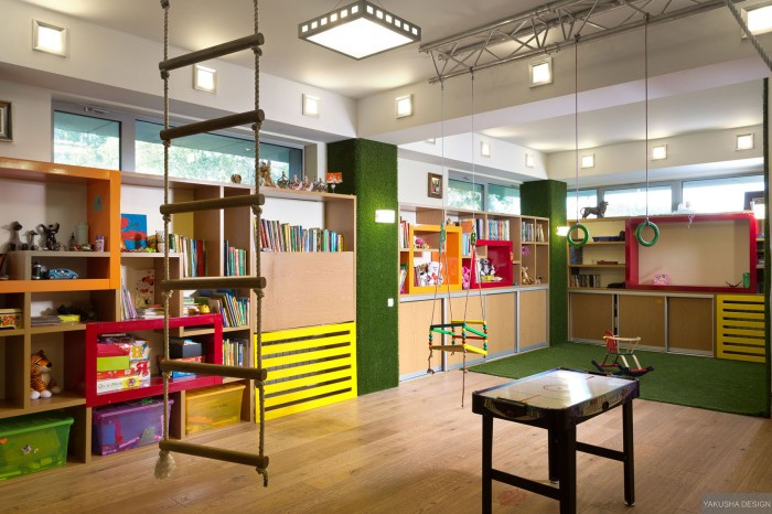 brightly colored childrens playroom with suspended swings and monkey bars