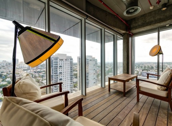 This quite workspace decorated as if a living room looks out over Tel Aviv and the country beyond.