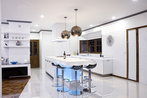 Traditional elements of wood molding, paneled doors and ornate wood flooring mix beautifully with harsher black and white plus metal elements in this modern kitchen.