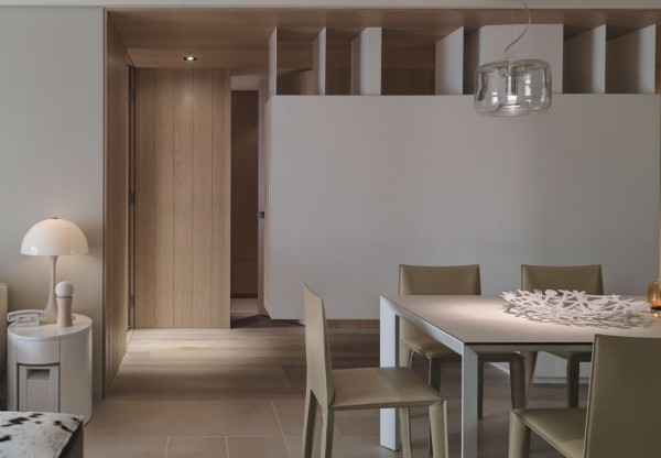 This view of the apartment shows the dining space in the foreground with a glimpse of the bedrooms beyond.