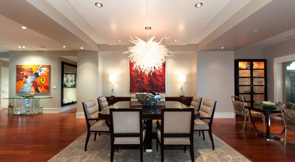 The full dining room sits within an open living space with seating area, piano, and eat-in kitchen.