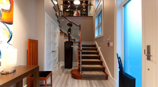 A small foyer boasts soaring 16' ceilings and walls of windows which fill the space with light.