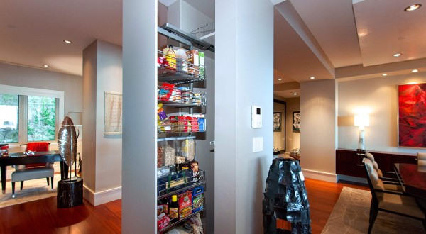 A hidden slide-out pantry fits into a dividing wall in the kitchen.