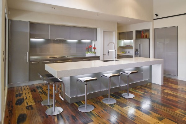 Warm wood plank flooring and plentiful light provide the perfect canvas for colder metal elements found in this modern kitchen.