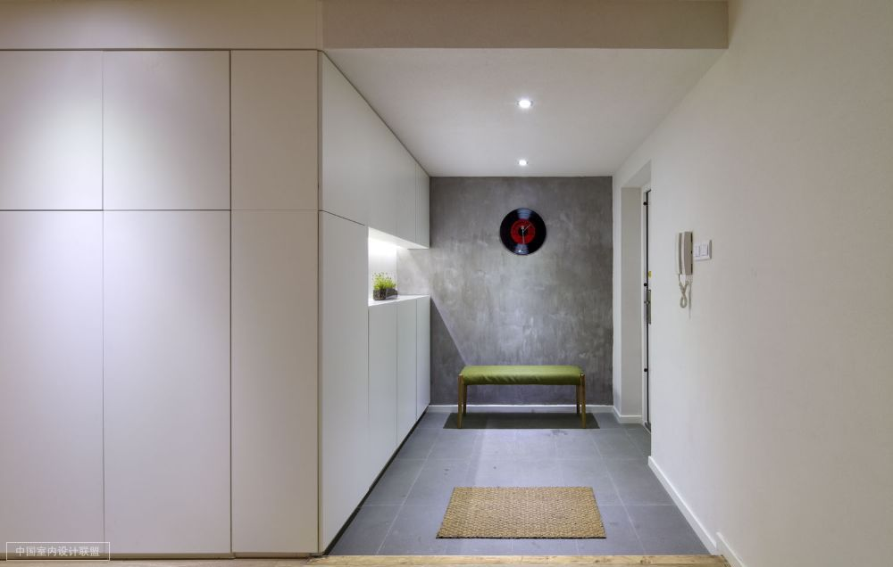 Simple storage in down lit hall with quirky record clock for Quirky apartment design