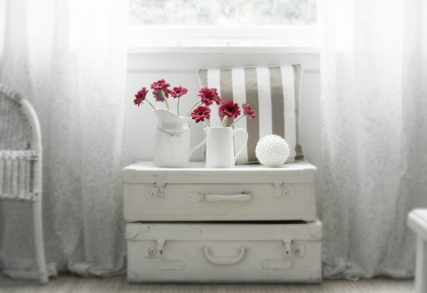 suitcase stack beneath window with crimson florals in jugs