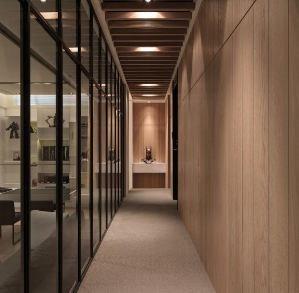The long hallway stretches the length of the living and dining spaces and is enclosed by a smoky glass wall.