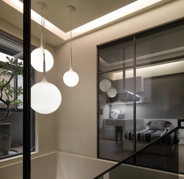 A simple modern opaque globe fixture lights the stairwell from the ceiling of the third level.