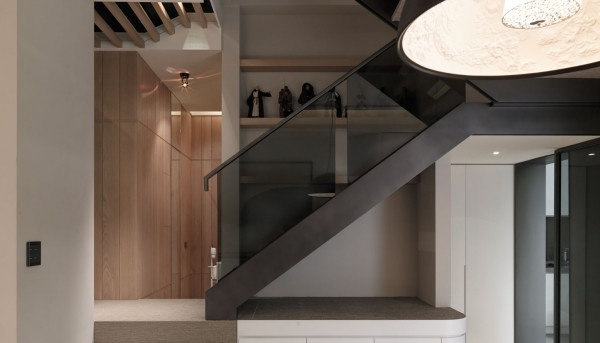 The staircase boasts a smoky glass railing framed in steel with display shelves in backdrop.
