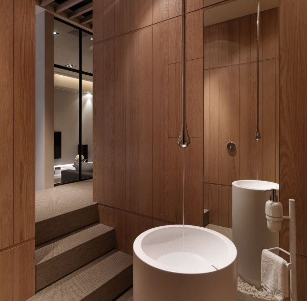The sunken bathroom boasts rich organic walls and round shaped basin with single bulb fixture above.