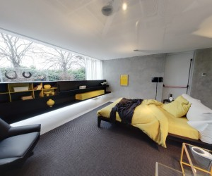yellow and grey bedroom with fitted storage and black leather armchair
