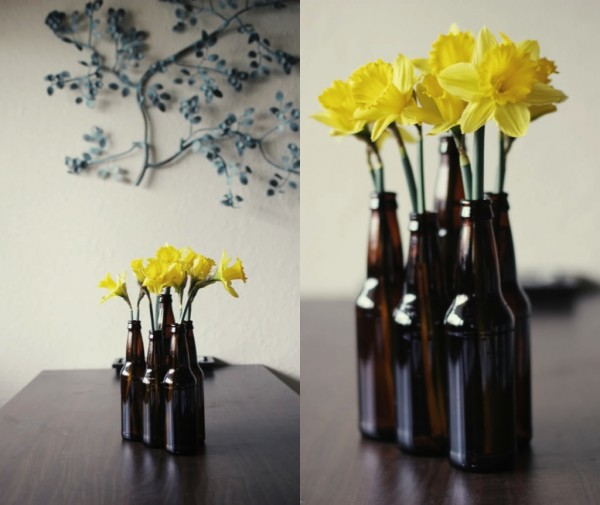 yellow dafodils in recycled beer bottles