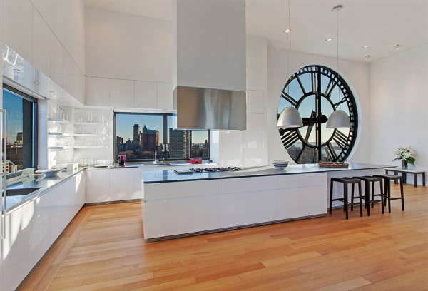 Clock Tower Apartment- glossy white open plan kitchen with island range and wood flooring