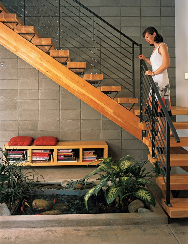 Dwell indoor fish pond viewed from rich wooden staircase