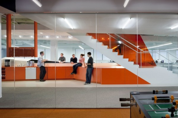 The glass-paneled staircase, in particular, fosters a hive of activity. Upon their descent, employees arrive at a coffee bar, which spans thirty feet and acts as the centrally located heart for Kayak's various departments.