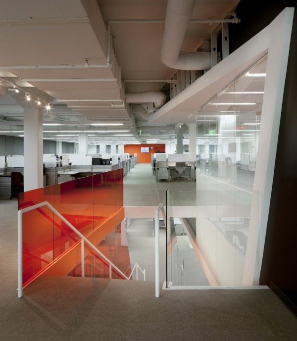 Kayak Startup Tech Office- glass panelled stairwell with view to open plan white and orange work stations