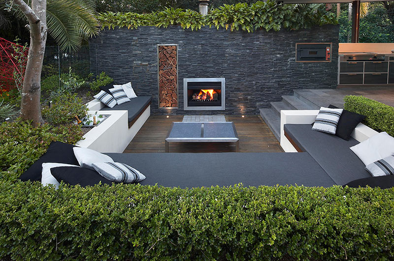 outdoor living with sunken lounge lit fireplace in stone
