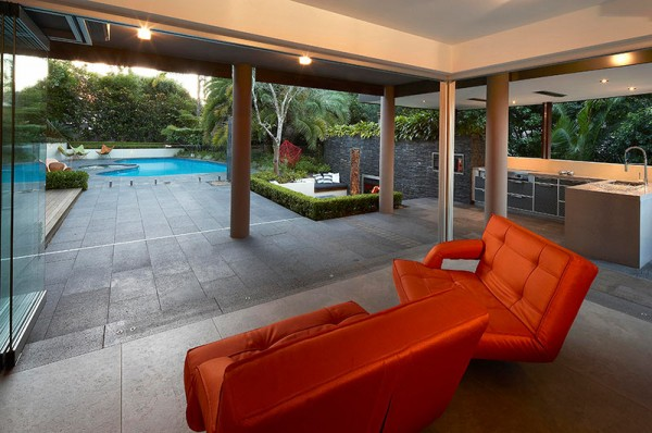Outdoor Living with Sunken Lounge- orange seating lounges undercover with views of garden