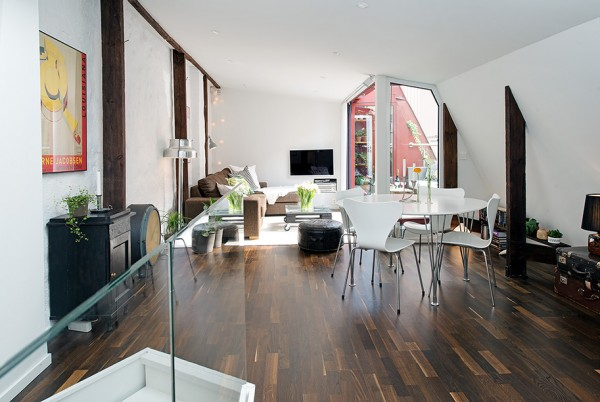 a Urban Apartment with Terrrace- white living broken by exposed beams and matching hardwood floors