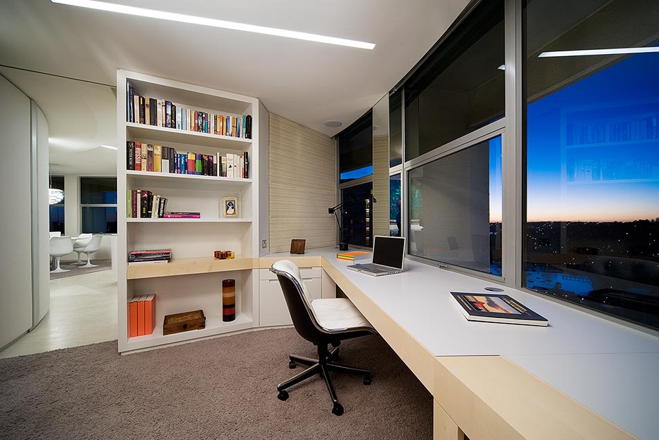 lengthy white and blonde wood desk workspace with city views