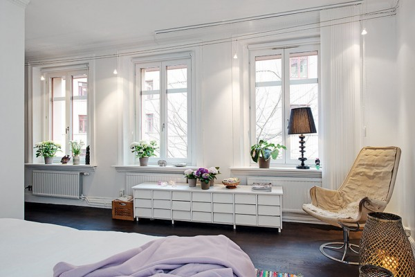 A combination of white walls and high ceilings can often times render a space arguably soulless and austere, but a sensitive approach to styling has resulted in cheer and charm that suggests a maternal influence befitting a space that includes a nursery.