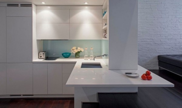 The resident is greeted by a compact corner kitchen. Down-lit and coated in a glossy white lacquer, it successfully conveys a modern yet simple aesthetic, which is particularly important in smaller spaces.