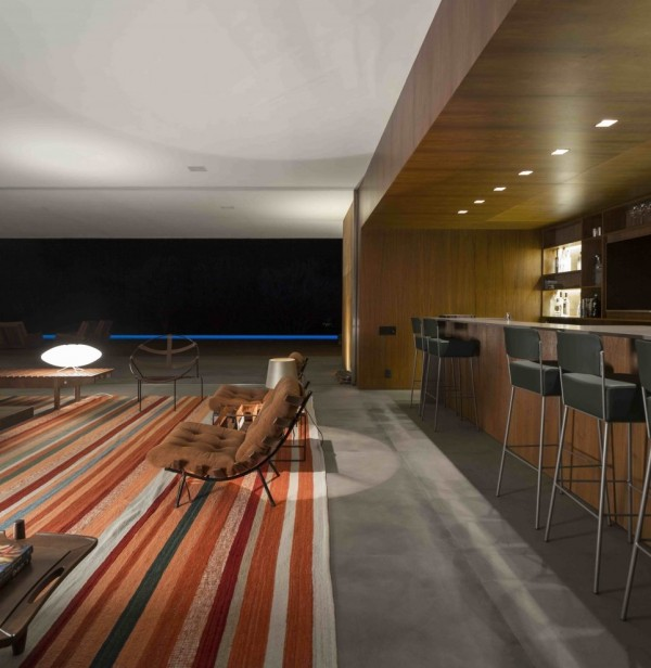 Marcio Kogan's Casa Lee Concrete House- bar living with wood clad and down lit outdoor views