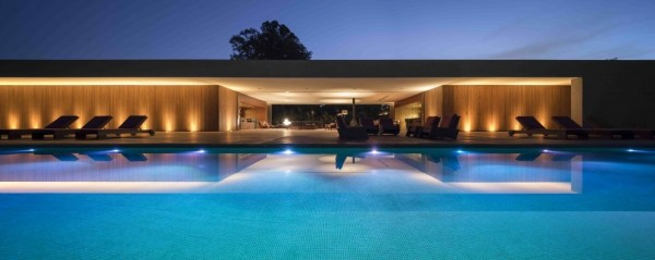 Marcio Kogan's Casa Lee Concrete House- view from illuminated pool to exterior at dusk