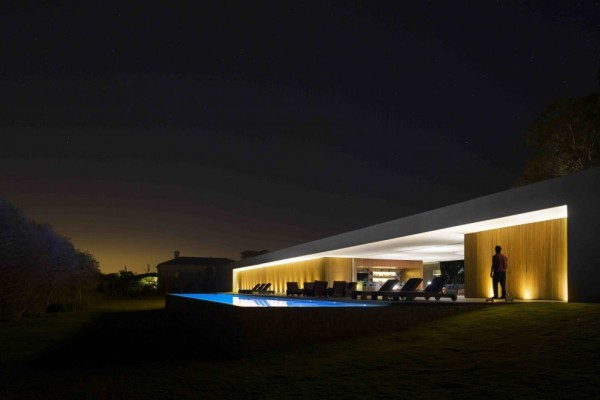 Marcio Kogan's Casa Lee Concrete House- view of exterior and pool at night