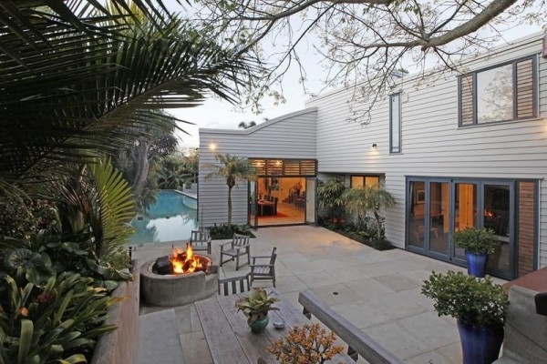 Sotheby's Auckland House- outdoor living with fire pit tropical gardens and pool