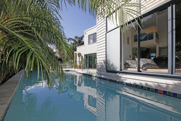 Sotheby's Auckland House- pool with overhanging palm fronds and view from window seat