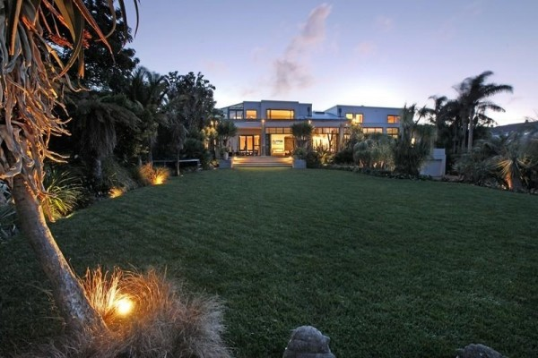 Sotheby's Auckland House- tropical garden lush lawn leading to house exterior