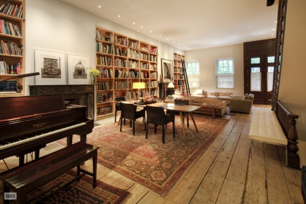 The main living space is warm and inviting with a brightly-hued oriental rug, a richly finished baby grand piano and built-in bookshelves.