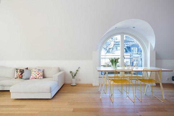 A niched eyebrow window adds architectural interest to the expansive white wall behind sofa and dining table.