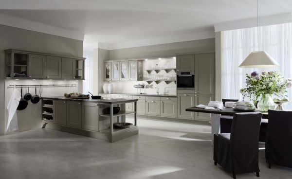 In a departure from a sleek façade that has not the need for handles, the cabinets featured in this image are altogether more reminiscent of a French farmhouse kitchen, albeit still a modern interpretation. The choice in flooring supports the exposed industrial display of the kitchen utensils, which hang atop a meeting of worktop and wall. It is interesting that Leicht has decided not to isolate the worktop in the typical kitchen island fashion, but viewers will notice the openness and sizable impression of the space, just as they will, the way in which this allows the honest flooring material to be showcased in its best light.