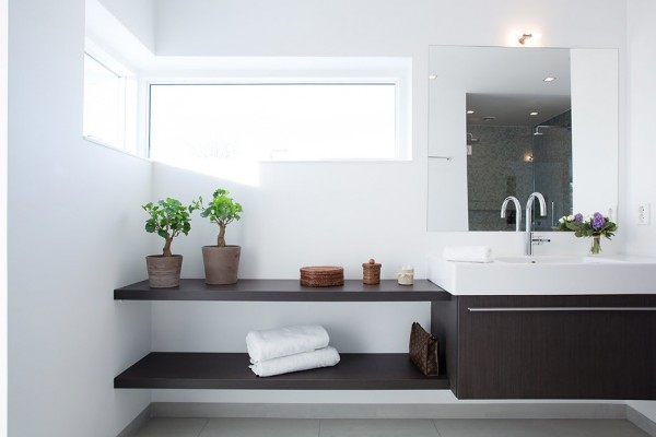 The built-ins in this modern bathroom are as aesthetically pleasing as they are functional. The dark wood of the vanity and shelves contrast nicely with the pristine white walls and floors.