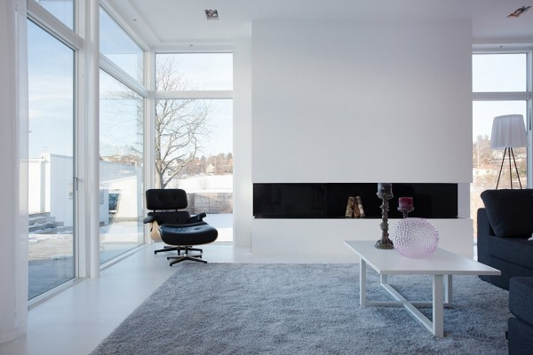 The central living room features a sleek fireplace surround with nondescript lines. An Eames Lounge Chair adds a touch of mid-century modern aesthetic.