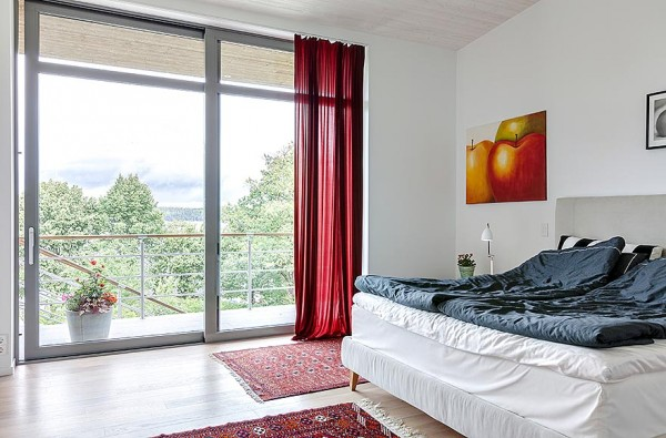 One of the villa's bedrooms provide views to the countryside beyond a large sliding door spanning from ceiling to floor. Red sheers add a nice touch of color to the space as does the art print and rugs.
