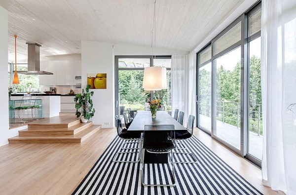 Dynamic black and white is the order of the day in the light filled dining space. In the large open space, the dining area is defined by a dramatic stripe rug under the dining table.