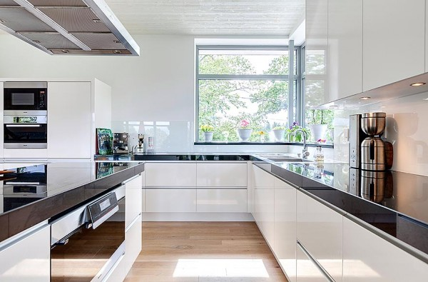 The kitchen is all about function in a sleek modern package. The black glass cabinet tops contrast nicely with the pure white space.
