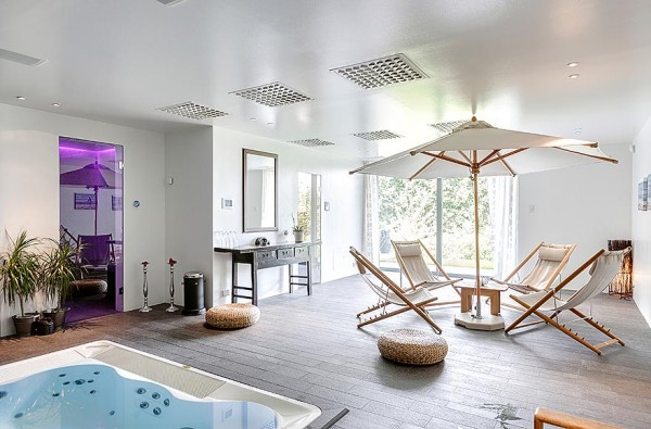 Who says umbrellas are for the outdoors only? This home spa boasts a natural wood and canvas fabric version. The sauna on the far wall is illuminated in a dramatic purple.