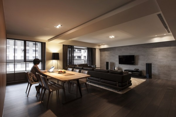 This moody open area living/dining space is filled with dramatic dark elements from richly-finished walnut floors to inky black velvet furnishings.